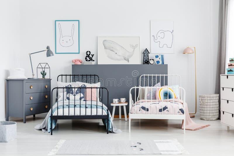 Camas blancos y negros en interior colorido del dormitorio de los niños con los posts fotografía de archivo