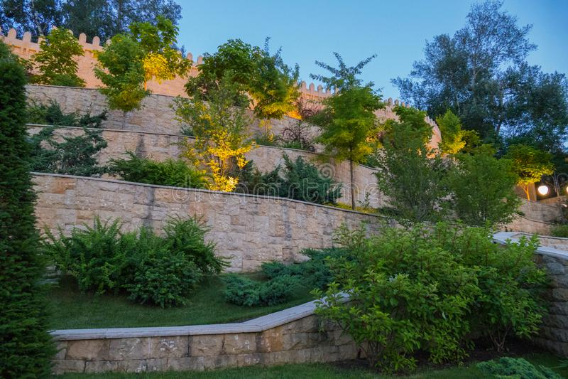 Camas de flor que crescem nas etapas da parede que vai acima Algumas plantas são iluminadas de baixo com das luzes para o efeito imagem de stock