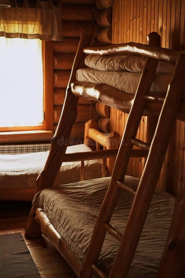 Camas de madeira do beliche em uma sala de madeira da pensão imagens de stock