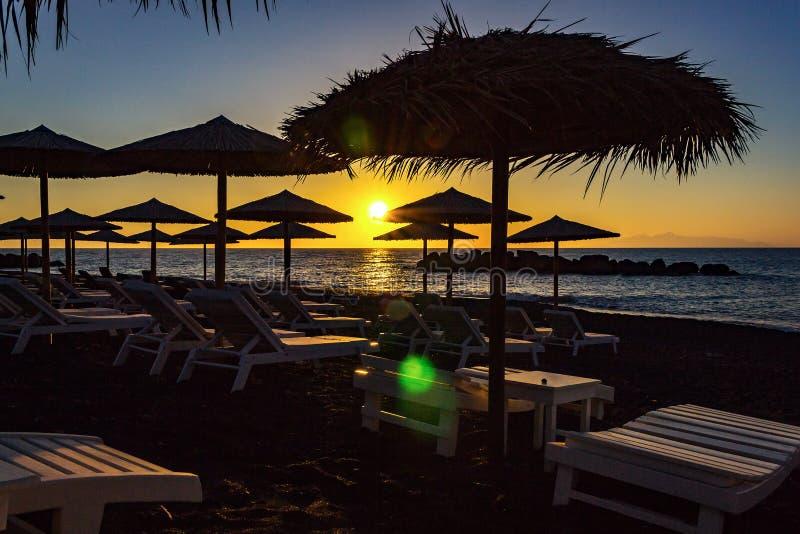 Camas de Sun durante o nascer do sol na praia de Kamari, Santorini, Grécia imagens de stock