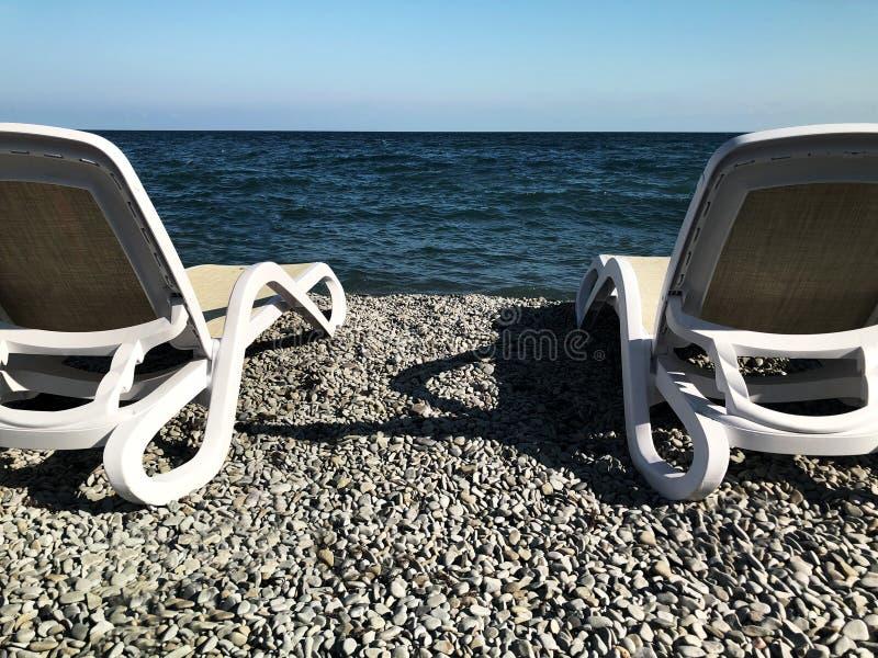 Camas de Sun en la playa de piedra imagen de archivo