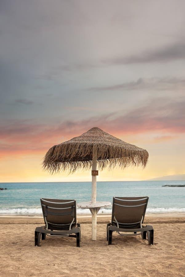 Camas do sol e guarda-chuva sós com ideia do por do sol impressionante - Tenerife, Ilhas Canárias fotografia de stock