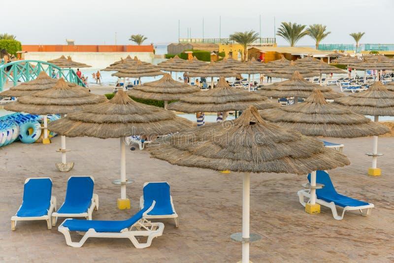 camas do sol no Sandy Beach mediterrâneo de turquesa profunda tropical popular do paraíso Guarda-chuvas no mar da praia o em um v fotos de stock royalty free