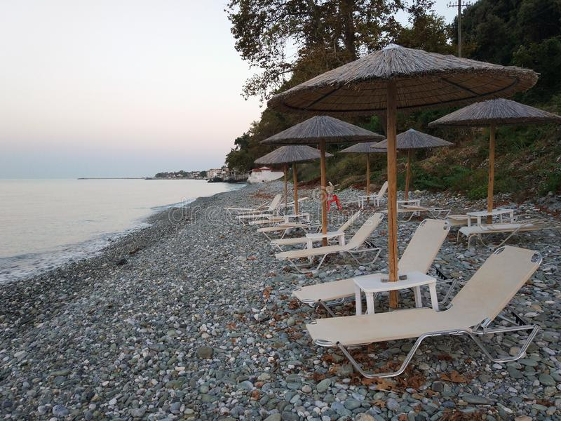Camas e guarda-chuvas da praia no por do sol imagem de stock