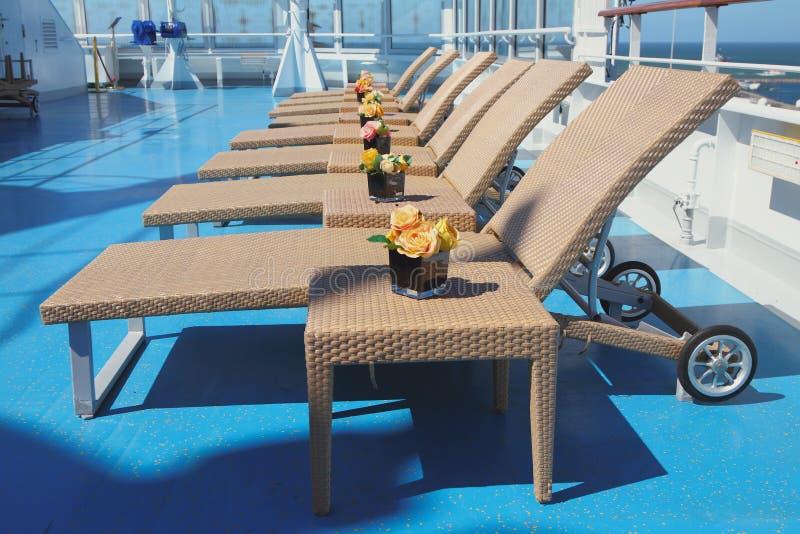 Camas e tabelas de Sun na zona da sala de estar na plataforma do forro do cruzeiro imagem de stock royalty free