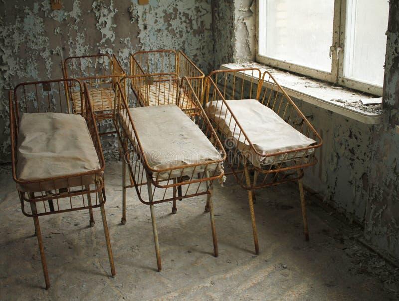 Camas para los bebés recién nacidos en hospital abandonado en Pripyat, Chernóbil, Ucrania fotografía de archivo libre de regalías
