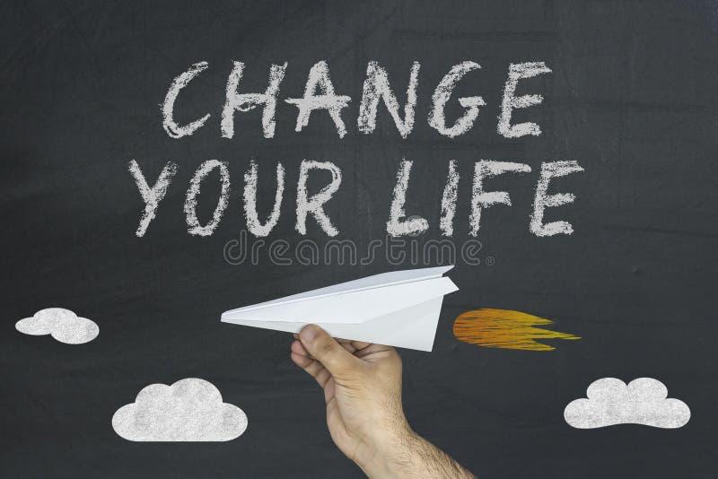 Cambi il vostro concetto di vita sulla lavagna con la mano maschio del ` s che tiene l'aeroplano di carta fotografia stock
