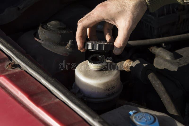 Cambiamento fluido di guida Il meccanico riempie il liquido del servosterzo del carro armato immagini stock