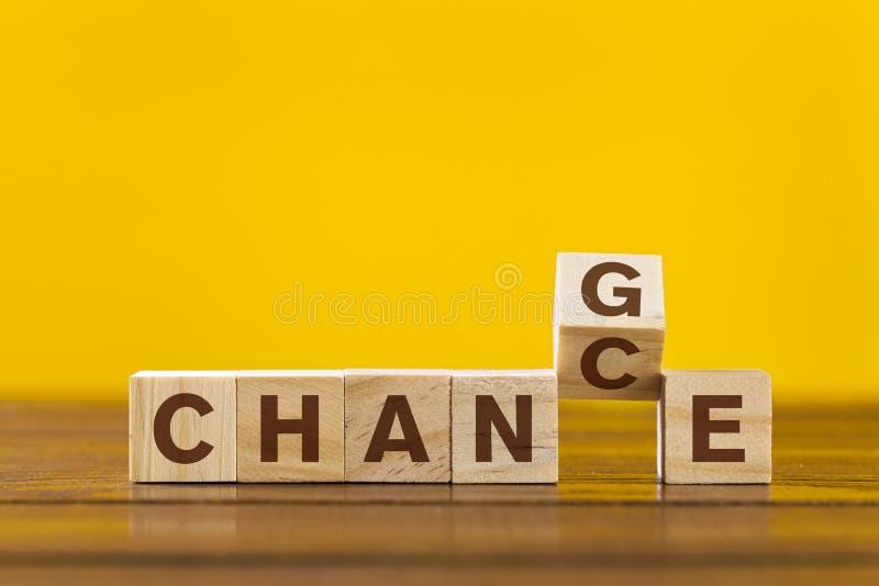 Cambie el concepto Letras de madera en un fondo amarillo fotografía de archivo
