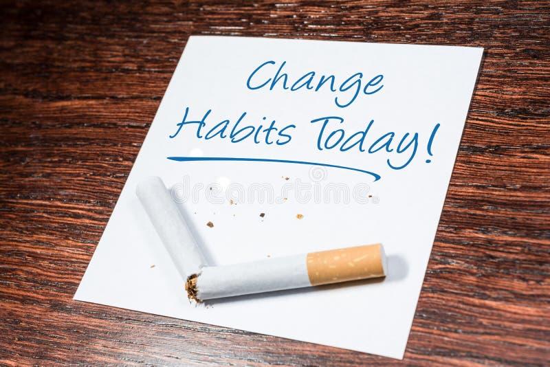 Cambie el recordatorio del vicio de fumar con el cigarrillo quebrado en estante de madera imágenes de archivo libres de regalías