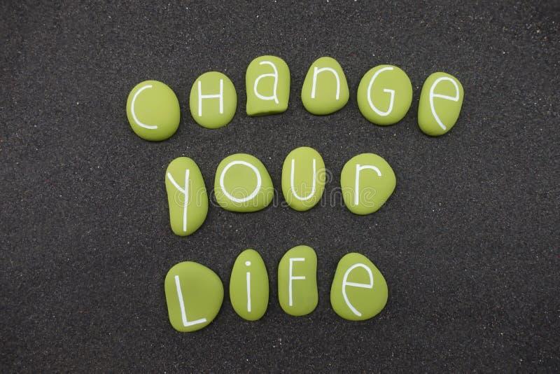 Cambie su lema de la vida con las piedras coloreadas verdes sobre la arena volcánica negra imagen de archivo libre de regalías