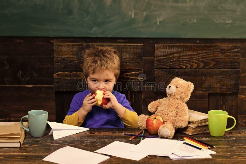 Cambio de la escuela Rotura de la escuela Manzana penetrante del niño hambriento en sala de clase Pequeño muchacho que juega con  fotos de archivo libres de regalías