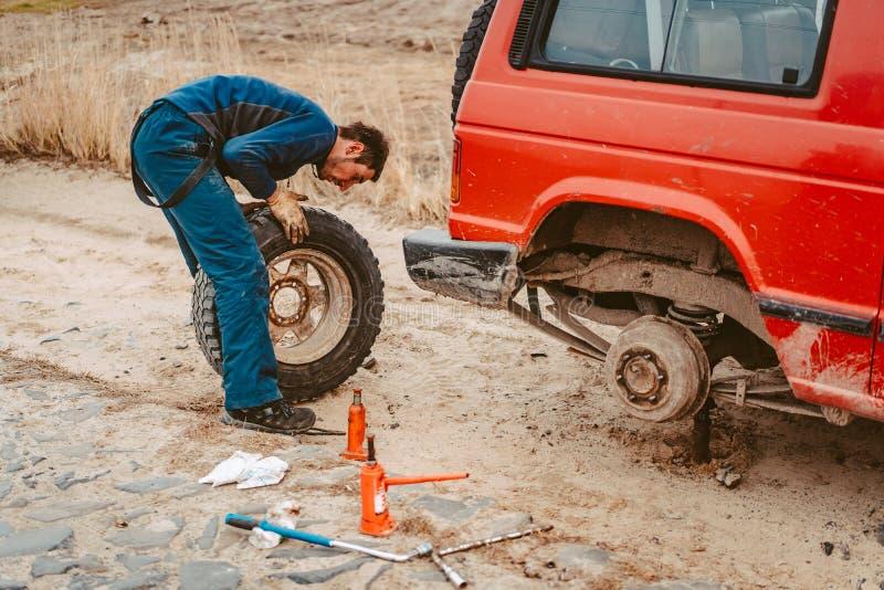 Cambio del hombre la rueda manualmente en un 4x4 del cami?n del camino fotografía de archivo