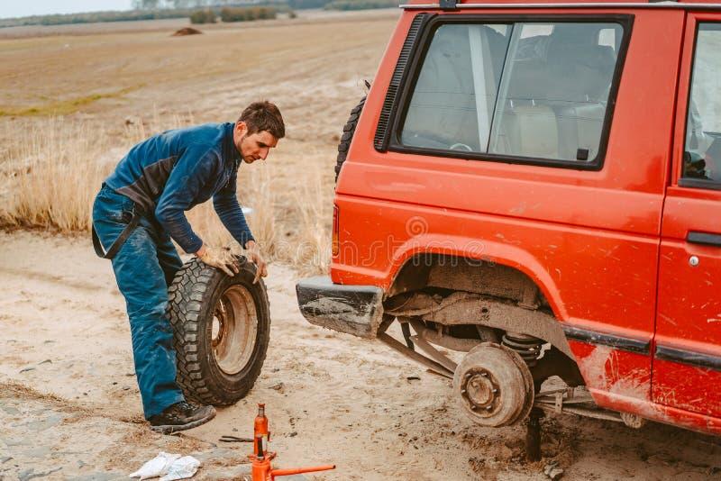 Cambio del hombre la rueda manualmente en un 4x4 del cami?n del camino foto de archivo libre de regalías