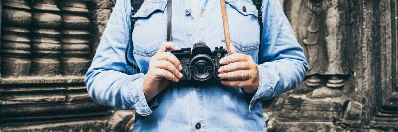Cambodge : Une femme en chemise en jeans tenant une caméra de cinéma vintage avec le temple d'Angkor Vat sur fond photographie stock
