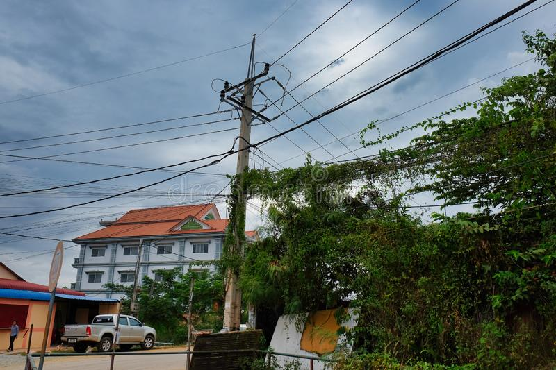 Cambodia, Siem Reap 12/08/2018 green thickets on the streets of the city, a pole of power lines in slums, urban jungle. Cambodia, Siem Reap 12/08/2018 green stock photography