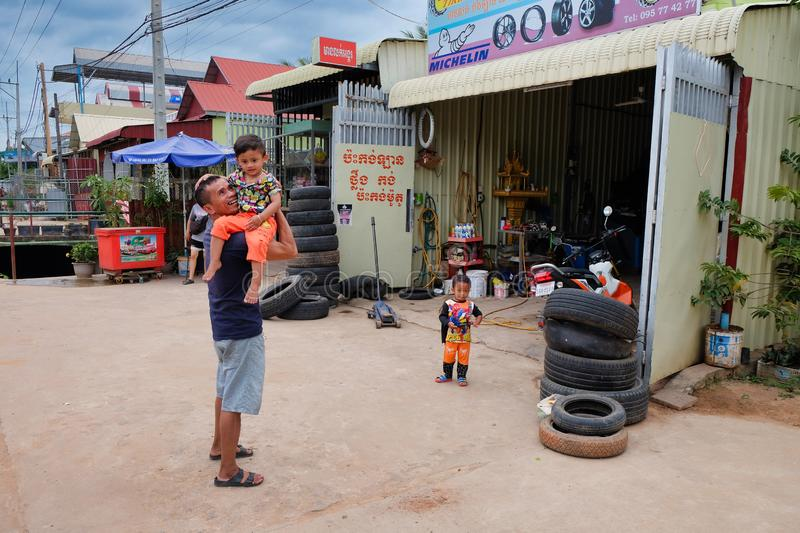 Cambodia, Siem Reap 12/08/2018 man with a child in his arms near the tire shop, slums of Asia, residents of poor areas of the stock photography