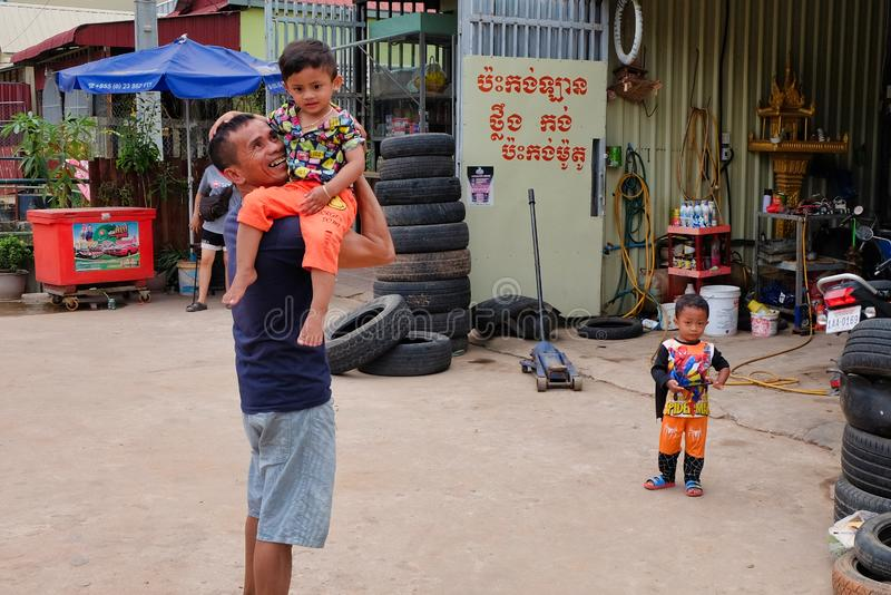 Man with a child in his arms near the tire shop, slums of Asia, residents of poor areas of the stock image