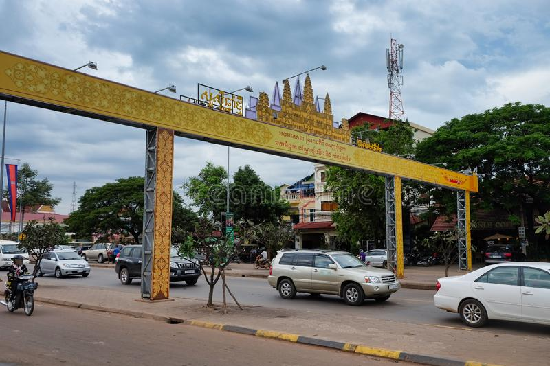 Cambodia, Siem Reap 12/08/2018 Motor traffic on a city street in southeastern Asia, cloudy weather, yellow arch with inscriptions. Cambodia, Siem Reap, Motor stock images