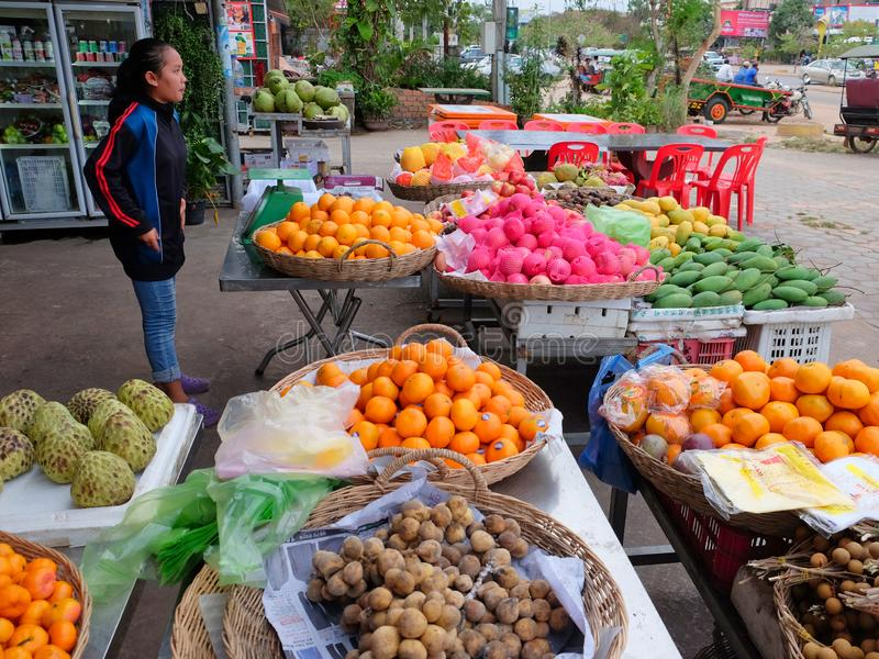 Cambodia, Siem Reap 12/08/2018 young Asian girl sells fruit on a city street. Cambodia, Siem Reap 12/08/2018 A young Asian girl sells fruit on a city street stock photo