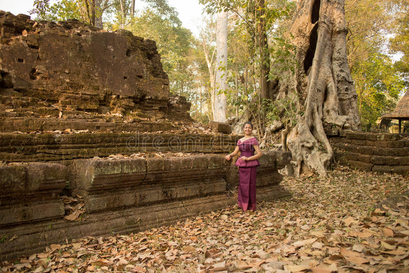 Cambodian Asian Girl in Traditional Dress by Ancient Temple Ruins in Angkor Thom stock photo