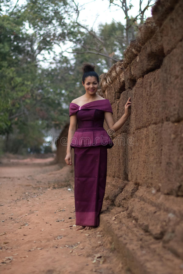 Cambodian Girl in Khmer Dress by the Ancient Wall of Phnom Bakheng, Angkor City. A Cambodian girl in a traditional Khmer dress by the wall at Phnom Bakheng royalty free stock images