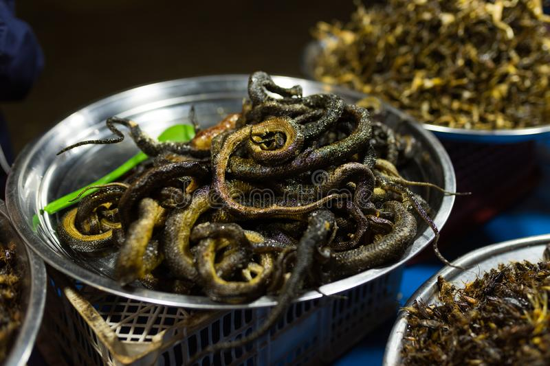 Cambodian night street food market with grilled snakes. In the iron bowl stock image