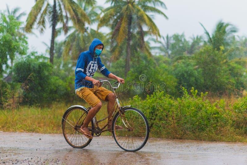 Cambodjaanse persoonscycli terwijl regen stock afbeeldingen