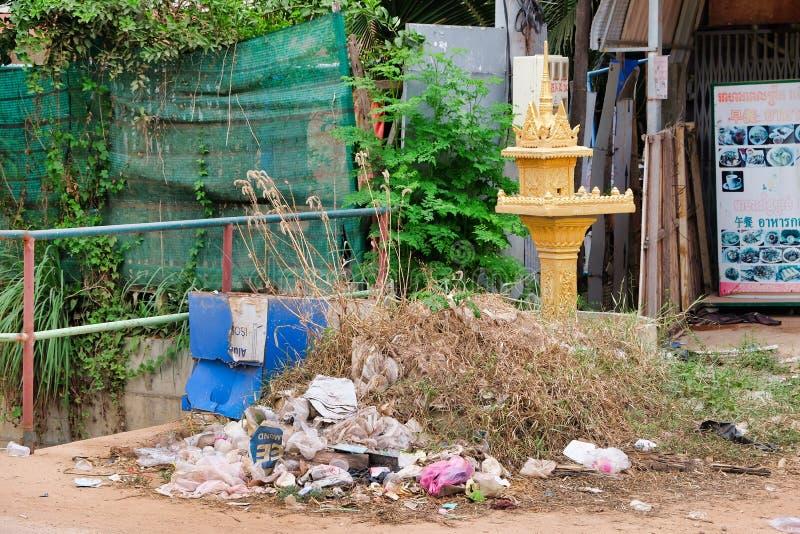 Camboya, Siem Reap 12/08/2018 pequeño santuario budista de a entre los montones de la basura en una calle de la ciudad, una desca foto de archivo libre de regalías