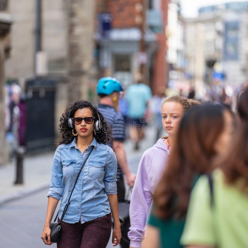 Cambridge, Großbritannien, am 1. August 2019 Porträt der schönen Mischrassefrau, die das Hören auf die tragende Kopfhöreranwendun lizenzfreie stockfotografie