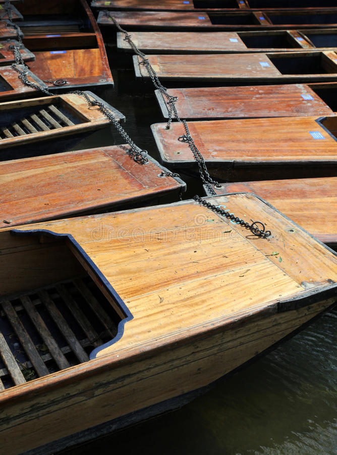 Cambridge punts. A group of wooden punts tied together on the river Cam in Cambridge - England. Punting is one of the university cities iconic activities stock image
