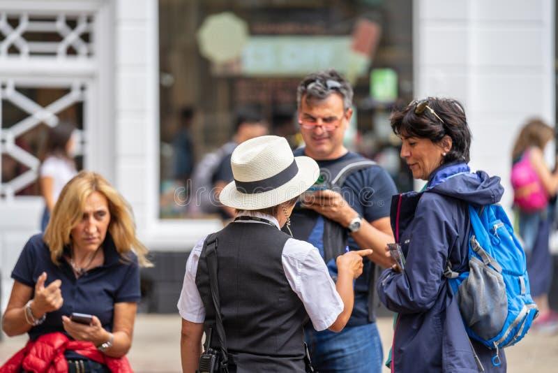 Cambridge, R-U, le 1er août 2019 Les touristes ont la conversation avec un membre de conseil municipal de Cambridge photos libres de droits