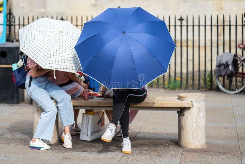 Cambridge, UK, August 1, 2019. Girls sitting On Bench Hiding Behind the Umbrellas royalty free stock photo