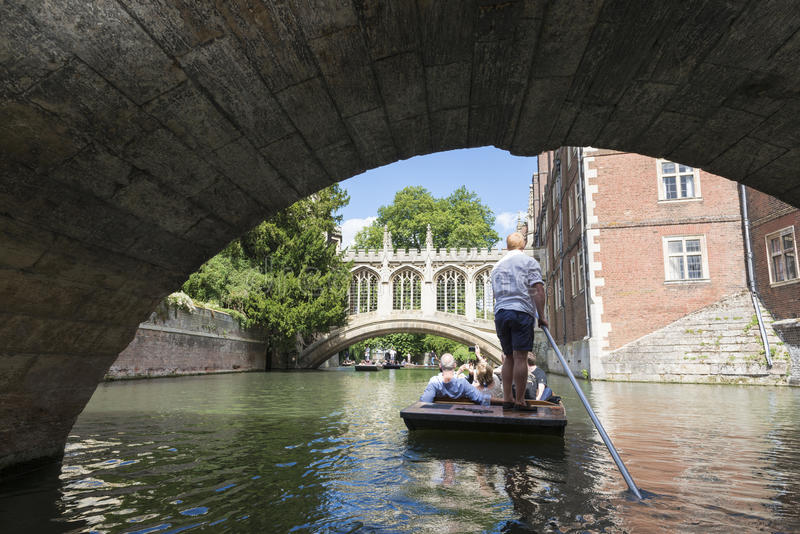 CAMBRIDGE, UK - AUGUST 18: Professional punter passing under the. Oldest bridge in Cambridge, Claire bridge, in busy River Cam and the Bridge of Sights in the stock photo