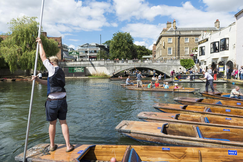 CAMBRIDGE, UK - AUGUST 18: Professional punter in Silver Street. With busy River Cam full of tourists in gondolas in background. August 18, 2013 in Cambridge royalty free stock photography