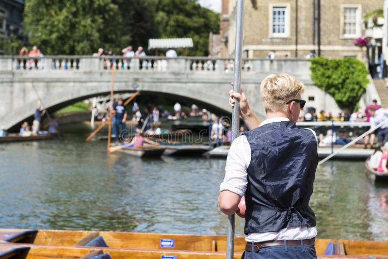 CAMBRIDGE, UK - AUGUST 18: Professional punter in Silver Street. With busy River Cam full of tourists in gondolas in background. August 18, 2013 in Cambridge royalty free stock photos