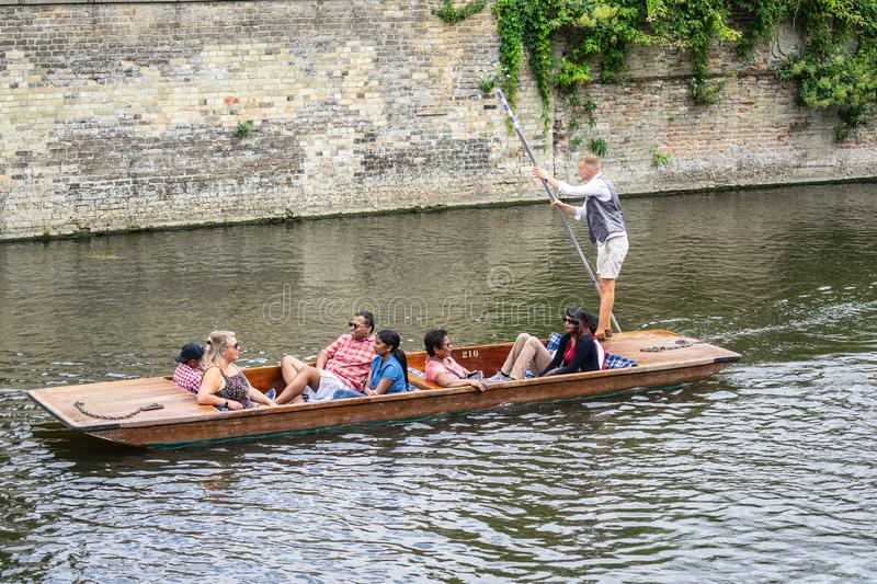 Cambridge, UK, August 1, 2019. The punter pushes a pole against the river bed and this gives the punt a way to move.  stock photography