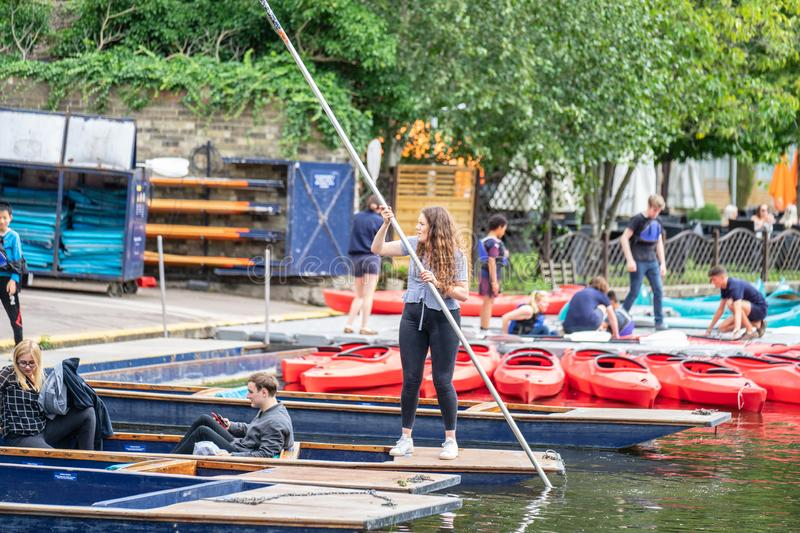 Cambridge, UK, August 1, 2019. The punter pushes a pole against the river bed and this gives the punt a way to move.  royalty free stock photo