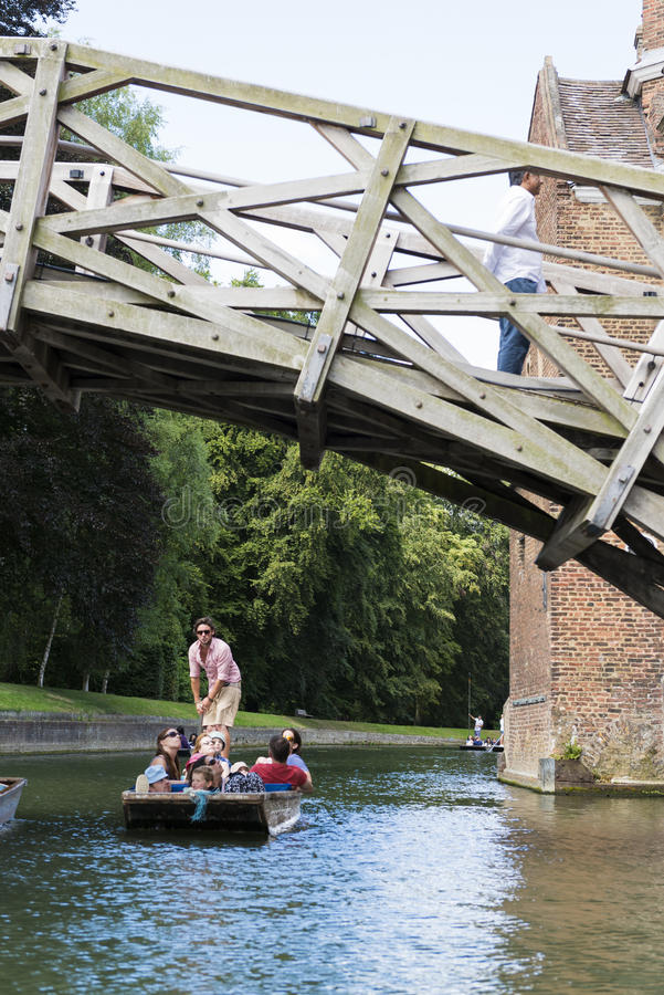 CAMBRIDGE, UK - AUGUST 18: Tourist punter in gondola in River Ca. M passing under Mathematical bridge with park full of trees in the background. August 18, 2013 stock photos