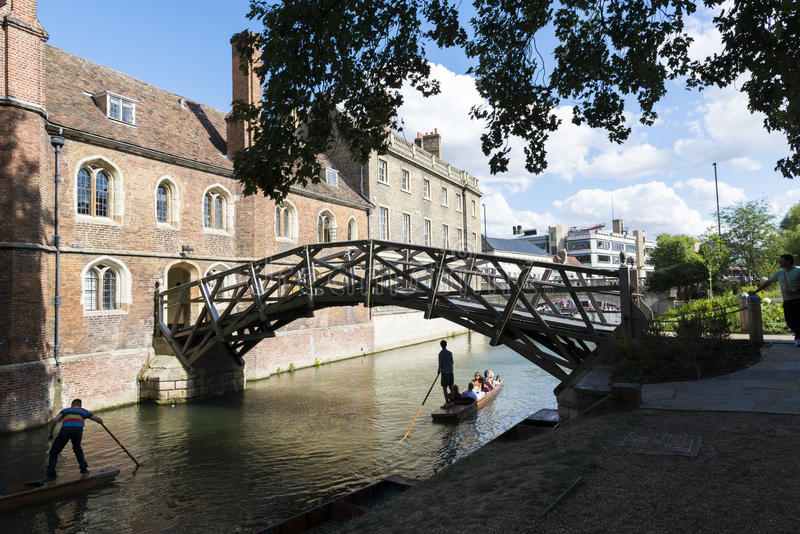 CAMBRIDGE, UK - AUGUST 18: Tourist punter in gondola in River Ca. M passing under Mathematical bridge with park full of trees in the background. August 18, 2013 royalty free stock images