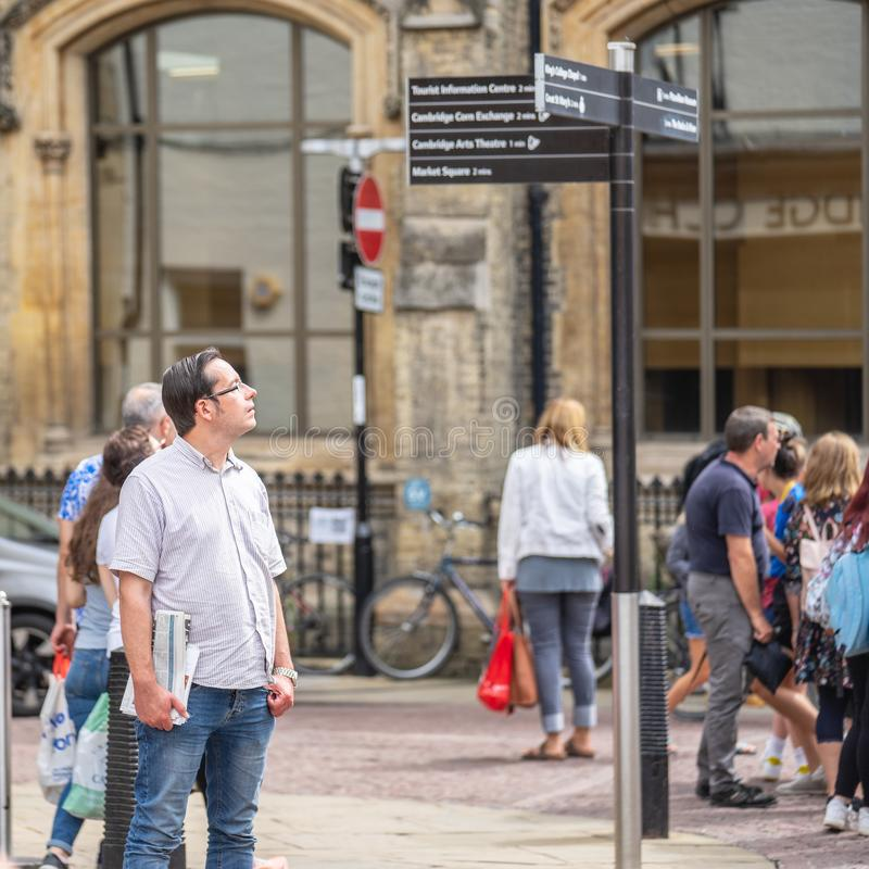 Cambridge, UK, August 1, 2019. Traveler reading directions at tourist attraction signpost with direction signs royalty free stock photos