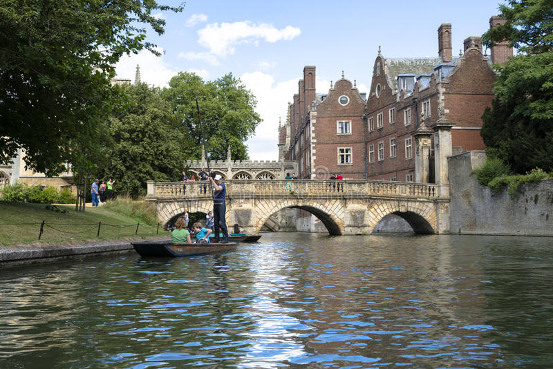 CAMBRIDGE, UK - AUGUST 18: Turist punter in River Cam with tree. Lined bank to one side and the olderst bridge in Cambridge, Claire bridge, followed by the royalty free stock photo