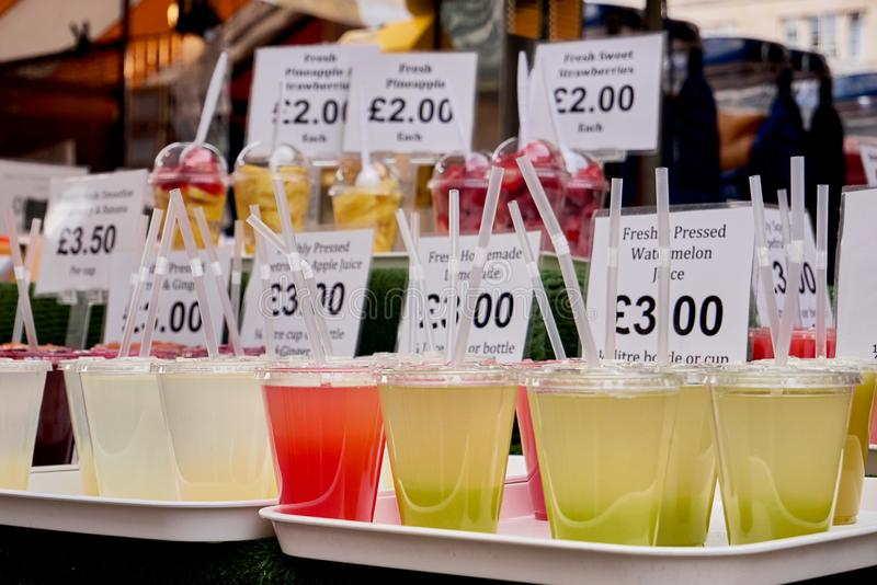 Cambridge, UK - October 9, 2019: Market stall with various fresh squeezed juices in plastic cups. Prices, fruit, healthy, orange, delicious, food, juicy stock photos