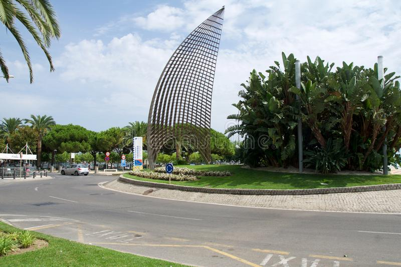 CAMBRILS, SPAIN - AUG 27th, 2017: Modern sculpture A tota vela, a round about and the main street promenade in the port stock images