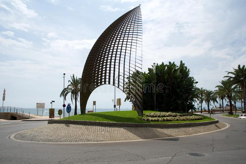 CAMBRILS, SPAIN - AUG 27th, 2017: Modern sculpture A tota vela, a round about and the main street promenade in the port stock photography