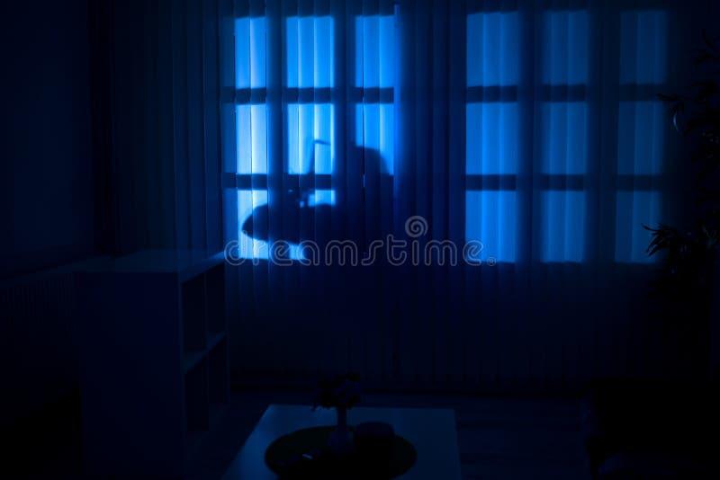 Cambriolage ou voleur pénétrant par effraction dans une maison la nuit photo stock