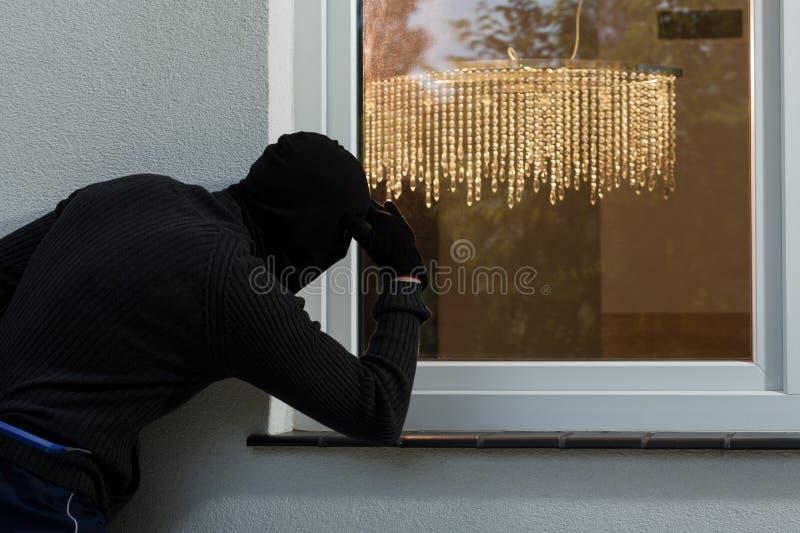 Cambrioleur à une fenêtre image stock
