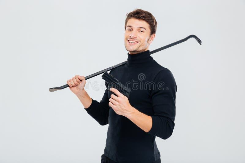 Cambrioleur criminel de sourire se tenant avec l'arme à feu et le pied-de-biche photographie stock libre de droits