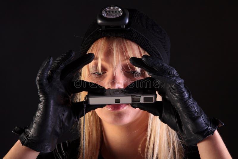Cambrioleur de chat blond de femme utilisant un appareil-photo d'espion photo stock