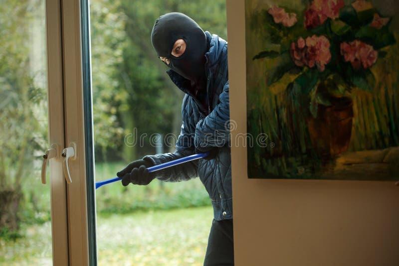 Cambrioleur derrière la fenêtre photos libres de droits